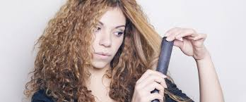 woman with curly hair using flat iron adobe
