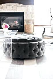 round charcoal gray tufted storage tucked under clear acrylic coffee table white