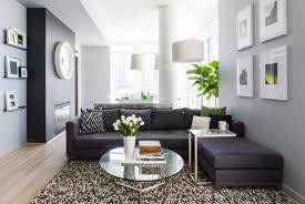 contemporary open concept living room with a ribbon fireplace light hardwood floors and gray walls dark gray sofa