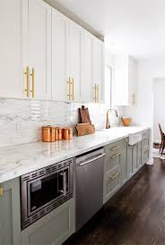 kitchen with gray lower cabinets and white uppers with brass hardware and marble countertops