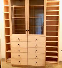 cabinets with glass doors and shoe shelves in walk in closet