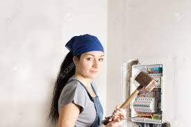 w electrician standing in front of an open fuse box stock photo w electrician standing in front of an open fuse box a wooden mallet in one hand and a screwdriver in the other as she contemplates