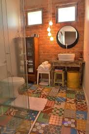 rustic bathroom with colorful patterned tile floor and exposed brick