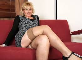 Older woman sitting on sofa wearing stockings looking for young.