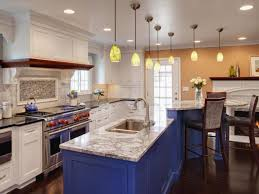 blue painted kitchen cabinets white marble countertop upholstered bar stools slide in gas range and hood 7 yellow pendant lights dark wood flooring