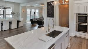 light color marble countertops kitchen island with sink cutout and countertop with white cabinets