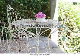 white wrought iron furniture. white wrought iron outdoor table and chairs on patio with vase of pink roses in south furniture g