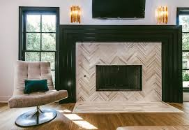 square rectangular brownish white travertine tile surround fireplace with black shiny polished fireplace mantel brown teak hardwood laminate flooring wall
