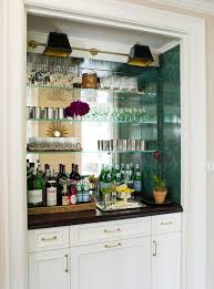 wet bar with mirrored back wall and glass shelves
