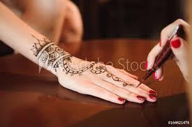 Fotografie Obraz Master Mehndi Draws Henna On A Female Hand