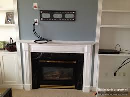 tv wall mount installation with wire concealment over fireplace simple design