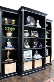 Trim three inexpensive bookcases with mouldings and paint them black...  they look great