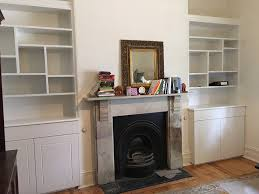 custom wall units and book shelves built around fireplace