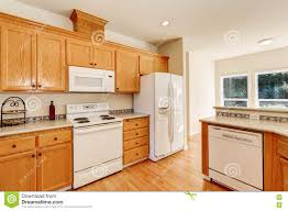 Light Brown Kitchen Cabinets And White Appliances Stock Photo