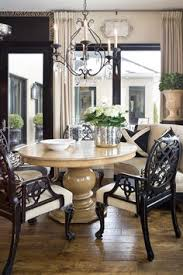 chic dining room with curbed mushroom linen bench round pedestal sining table black dining chairs iron crystal chandelier and mercury gl bucket
