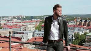a trendy man in a black leather jacket and white shirt standing outdoors with a great view of a city behind him on a sunny summer day