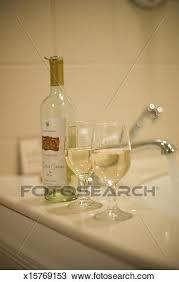 bottle of wine and glasses on bathtub