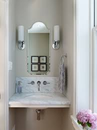 small powder room features polished nickel sconces flanking frameless arched mirror over white marble floating vanity accented with wall hot and cold faucet