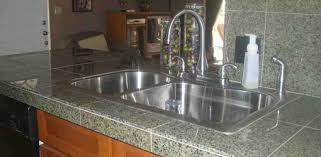 sink and faucet installed on granite tile countertop