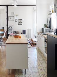 the raised kitchen island in this home bridges the gap between the kitchen tile and the