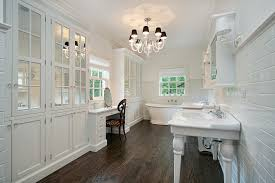 This lengthy white bathroom features rich, dark hardwood flooring for a  striking, high contrast