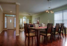 formal dining rooms with columns. transitional dining room with chandelier, crown molding, columns, hardwood floors, high ceiling formal rooms columns