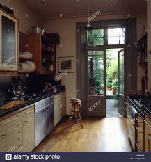 The Garden Kitchen Wooden Flooring In Modern Galley Kitchen With French Doors Open To