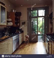 The Garden Kitchen Wooden Flooring In Modern Galley Kitchen With French Doors Open To