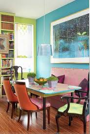 Bright Dining Room With Orange Ack Chairs Colorful Tale Paint Pendant Lamp  And Pink Sofa With Blue Green Wall Paint And Wooden Floor Image