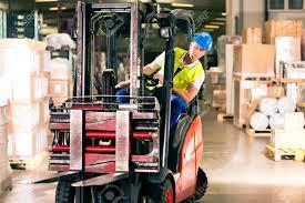 Forklift Driver In Protective Vest Driving Forklift At Warehouse