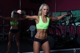 female fitness model in black pants and green crop top