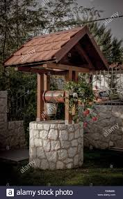 Modern Water Well Design Stone Well With A Wooden Roof And A Bucket Of Water In