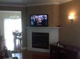 corner tv mounted over white fireplace as well as hiding wires for wall mounted