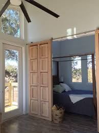 two sliding barn doors open to reveal a master bedroom the door in picture above contains the two eight foot long benches the other door which is not