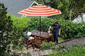 two people sitting at wooden patio furniture in a lush backyard underneath a striped patio