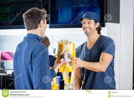 worker selling popcorn to man at concession stand stock photo smiling seller giving popcorn to man at concession stock images