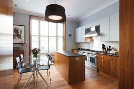 Example of a trendy l-shaped medium tone wood floor eat-in kitchen design