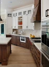 allwood cabinets transitional kitchen and dark stained wood glass upper cabinets hood kitchen peninsula natural wood floor open shelving pleated roman