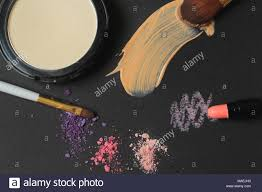 close up makeup brushes powder and cream strokes on black background