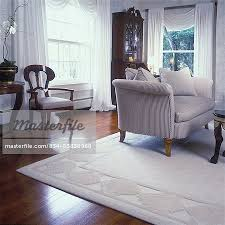 living rooms off white sculptured area rug white walls wood floors traditional upholstered love seat beige mahogany secretary stock photo