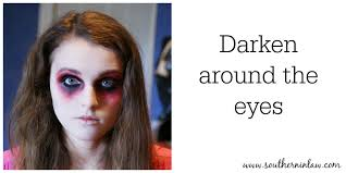 darken around the eyes with black face paint or eye liner zombie makeup tutorial step