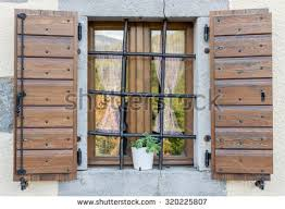 a nice window with open brown wooden shutters and curtains r1 shutters