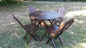 dark wood round garden table and 4 matching chairs 3ft wide by 28 inch high