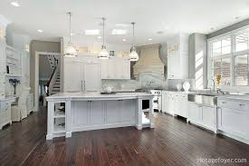 dark toned hardwood flooring white shaker cabinetry design large open concept a sink and stainless steel appliances