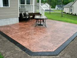 stamped and stained back yard patio with black stained concrete edge and rustic red concrete inside