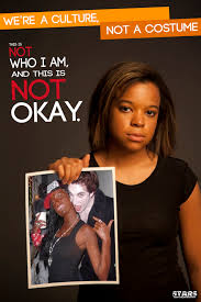 a young unsmiling black woman holds up a picture of a white woman in black