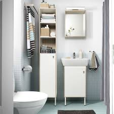 brown bathroom furniture. a small bathroom with light blue floor tiles white high cabinet mirror brown furniture