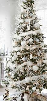 Holiday decorating - White on white Christmas tree with woodland creatures  and white branches.