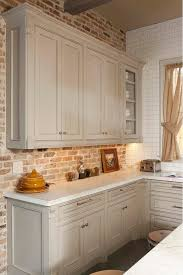 Gray kitchen cabinet with brick backsplash wall and honed Carrara  countertop. Whitestone