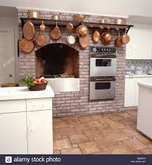 Kitchen Alcove Copper Pans On Rack Above Double Ovens And Hob Fitted Into Brick